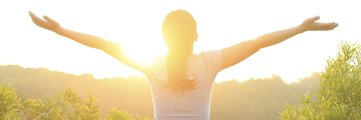 Woman with open arms in front of sunrise
