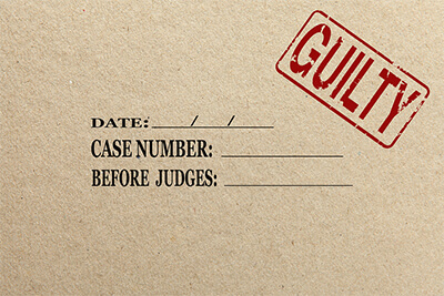 Paper texture with red guilty rubber stamp court folder